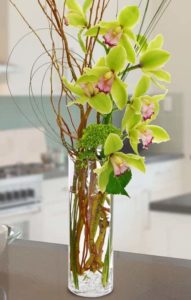 This simplistic, yet premium arrangement of lime green Cymbidium Orchids accompanied by loops of greenery and tall Curly Willow in a clear cylinder vase is made for a memorable statement that won't soon be forgotten!