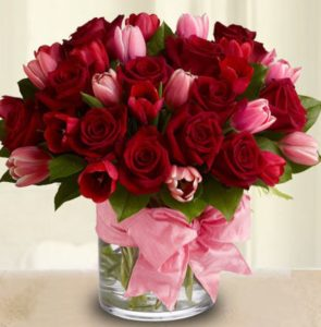 romantic arrangement of deep red roses accented with pink and red tulips, complete with a pink satin ribbon.