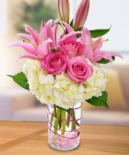 """Let someone special know you are thinking of them and sending """"Happy Thoughts"""" with this lovely design of white hydrangeas, elegant pink lilies, and Sweet Unique Roses."""